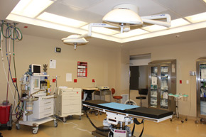 A surgical bed is surrounded by a equipment and supplies in the operating room at the Plastic Surgery Center of Westchester.